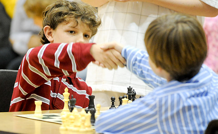 Appariement échecs : deux enfants se serrent la main avant de commencer une partie d'échecs. L'un habillé en rouge l'autre en bleu. Devant eux se dresse posé sur une table un jeu d'échecs en palstique et vinyle