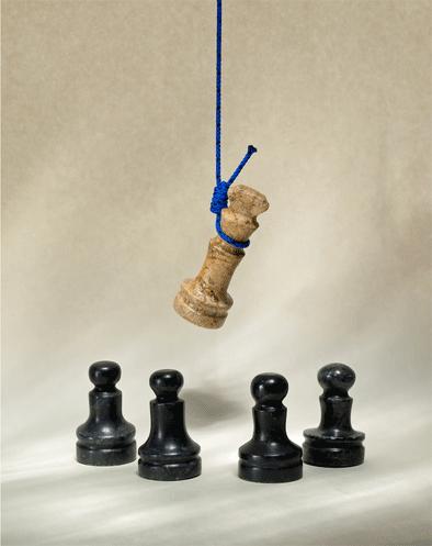 Echec et mat, le roi est pendu par une corde ficelle bleue et les pions noirs sont autour et regardent le roi mort