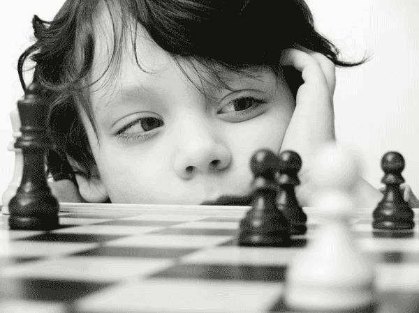 Enfant qui réfléchit devant un jeu d'échecs