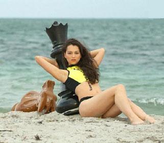 Alexandra Kosteniuk, étendue, presque allongée sur la plage en maillot de bain