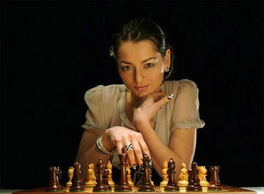 La jolie Alexandra Kosteniuk, nous regarde et se touche le cou