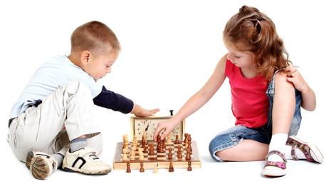 Deux anfant jouent aux échecs, un petit garçon et une fille, ils sont assis par terre. La fille a un tshirt rouge. Il y a une pendule à côté d'eux