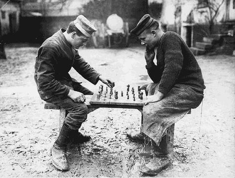 Deux hommes jouent aux échecs. Ils sont assis sur un banc fait de planches, l'échiquier est posé en équilibre. Ils portent de petits chapeaux ronds, un pull et un tablier pour le second. Ces hommes ne sont pas particulièrement détendus. Ils se sont pas à l'aise sur leur siège. Leurs épais souliers les protègent d'une boue grasse et humide. Certainement ces joueurs sont des travailleurs en pause, comme l'attestent leurs vêtements.