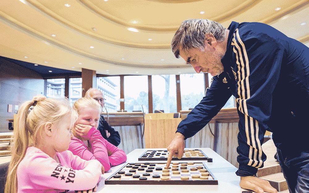 Le joueur d'échecs Vassily Ivanchuk en pleine simultanée de Jeu de Dames. contre de jeunes enfants