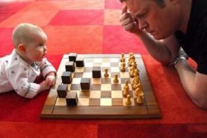bébé qui joue aux échecs contre son papa ou un monsieur qui réfléchit