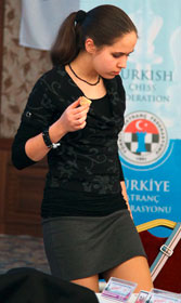 Joueuse d'échecs (Nastassia Ziaziulkina) en jupe courte en train de manger un gâteau