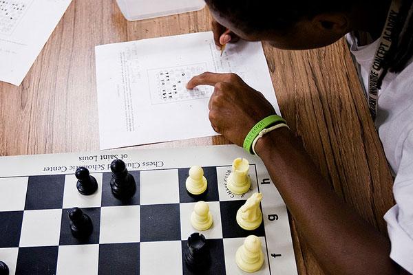 Jeu d'échecs : écrire, noter les coups (enfant qui écrit sur une feuille blanche)
