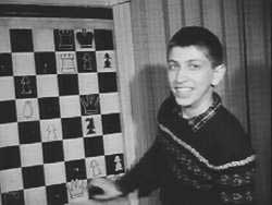 Bobby Fischer jeune, en pull, en train de sourire devant un échiquier mural